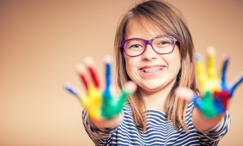 kid smiling with paint on hands