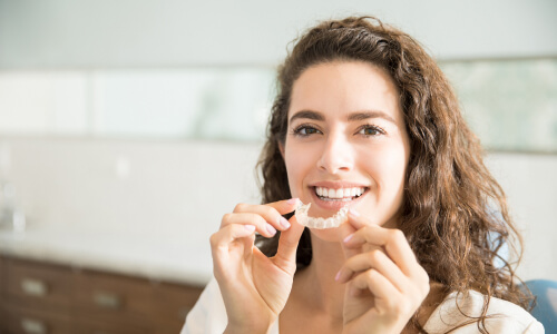 woman putting in her clear aligners