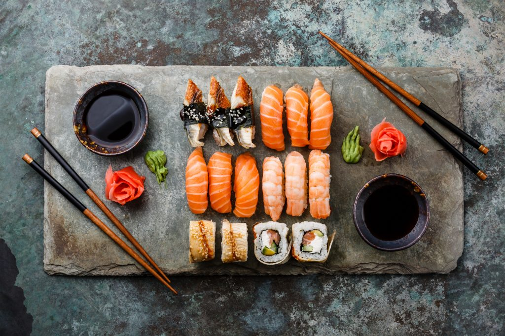 Sushi platter with a variety of rolls and fresh fish with chopsticks and soy dishes