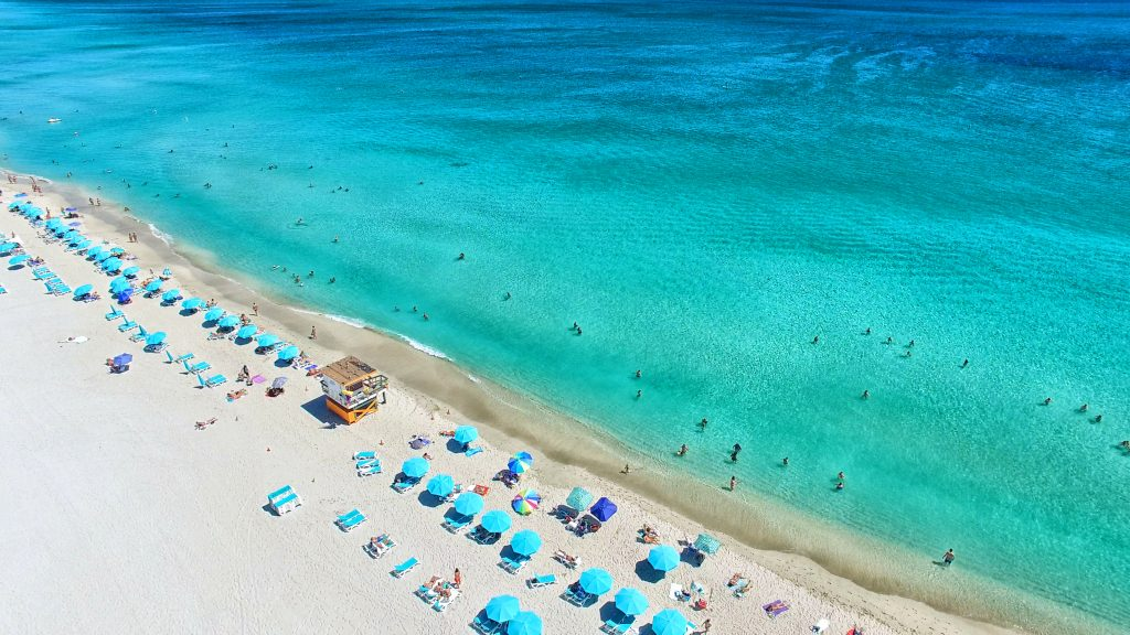 Aerial view of South Beach in Miami, FL with cabanas and pale green and blue ocean