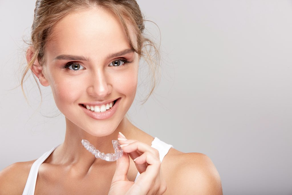 Young blonde-haired woman wearing white tank top and holding Invsialign - Is Invisalign Painful?
